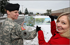 Army Col. Cynthia Murphy, left, and Morri Landes, hold illustrated proposals on Pendleton Avenue, the main street where plans are underway to build a downtown community at Fort Lewis, Wash.