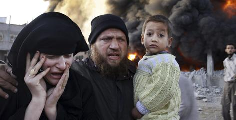 A Palestinian family rushes past a burning building on Sunday after an Israeli missile strike in the Rafah refugee camp, southern Gaza Strip.