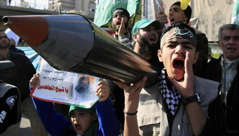 A Lebanese protestor shouts slogans as he holds a replica of a rocket during a protest against Israeli attacks on Gaza, in Beirut near government palace Sunday.