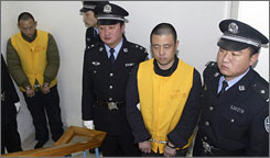 Defendants Zhang Yujun, right, and Zhang Yanzhang, left, are part of six on trial for their part in a tainted milk scandal that killed at least six kids and made hundreds of thousands of others ill.