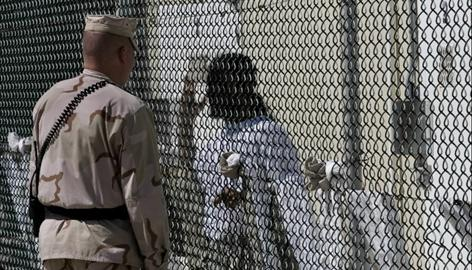 A guard faces a detainee at Guantanamo Bay Naval Station in Cuba. The Pentagon considers about 110 inmates too dangerous to ever be freed.