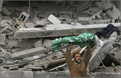 A Palestinian shouts as he lifts the body of a victim of an Israeli missile strike upon the Jebaliya refugee camp in the Gaza strip on Monday.  Five members of one family, including three children and two teenagers, were among those killed in two new air raids.