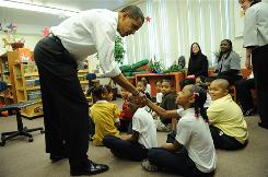 "President-elect Barack Obama shakes hands with a student at the Dodge Renaissance Academy in Chicago, Dec. 16. Obama vowed new funding for schools plus new demands on teachers and parents, arguing it was ""morally unacceptable for our children and economically untenable for America"" to allow standards to slip further."