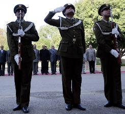 Members of the Iraqi National Forces salute during a flag-raising ceremony Jan. 1 outside the former palace of executed dictator Saddam Hussein in the Green Zone in Baghdad.