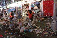 Strong winds lift debris from the New Year's celebration as sanitation workers clean up early New Year's Day Thursday, in New York's Times Square.