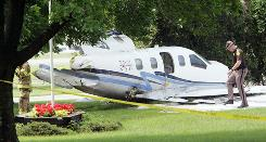 An Iowa State Patrol officer investigates the crash of a charity plane that killed a Georgia toddler in June.
