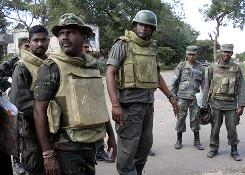 Sri Lankan army soldiers stand on a road Jan. 2  in the town of Kilinochchi. Sri Lankan attack helicopters bombed Tamil Tiger positions in the north of the island, the military said, a day after ground forces seized the rebel headquarters town of Kilinochchi.