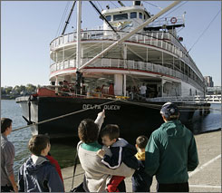 A family views the riverboat Delta Queen as it is docked on the public landing on the Ohio River in Cincinnati in 2008.