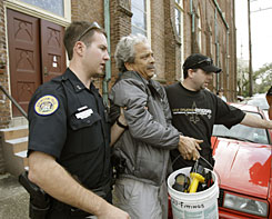 New Orleans Police officers remove a parishioner from Our Lady of Good Counsel Catholic church in New Orleans Tuesday. He was one of two congregation members that police arrested after they occupied the building to protest its closure by the Archdiocese of New Orleans.