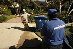 Los Angeles Department of Water & Power conservation team member Alonzo Belanger, right, talks to a gardener after he caught him watering a driveway in Beverly Hills, Calif., on Oct. 21, 2008. A total of 15 officers now prowl neighborhoods and respond to thousands of tips in their search for those who use sprinklers between 9 a.m. and 4 p.m., clean driveways with water instead of a broom or otherwise waste the precious commodity.