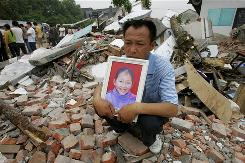 A man sits in the ruins of the Fuxin No. 2 Primary School in China's Sichuan province on May 23, holding a photo of his daughter, who was killed in the earthquake.