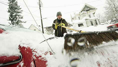 Neal Treece sweeps snow off his girlfriend?s car in Spokane, Wash. About 7 inches of snow fell on the area Tuesday.