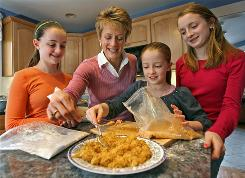 Dietitian Elizabeth Ward and her daughters, from left, Hannah, Emma and Hayley Loughlin, prepare an inexpensive but healthy and kid-approved dinner at their home in Reading, Mass.