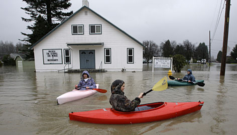 Kayakers Matt Laird, left, Willie Jensen and Ben Larson, all 17, paddle through a flooded street Wednesday near downtown Snoqualmie, Wash.