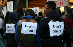 "Protestors wear signs on their backs that say ""don't shoot,"" during a demonstration at the Fruitvale BART station on Jan. 7.  Dozens of black community leaders and residents berated Bay Area Rapid Transit officials for hours at a meeting Thursday, the morning after demonstrators torched cars, smashed store windows and threw bottles at officers in downtown Oakland."