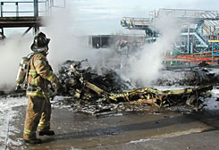 A Charlotte firefighter works to extinguish the blazing fuselage of a U.S. Airways Express aircraft at the Charlotte Douglas International Airport in Charlotte, Jan. 8, 2003. All 21 people aboard died in the crash. No airline passengers have died in the last two years on a U.S. carrier.