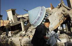 A Palestinian collects pages of the Koran Sunday from the ruins of a mosque destroyed by an Israeli air strike. Israeli forces edged into the most populous area of the Strip Sunday, killing at least 14 Palestinian guerrillas and 12 civilians.