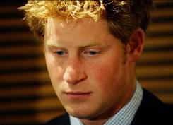 Prince Harry listens as his brother Prince William delivers a speech on Jan. 8 in London.