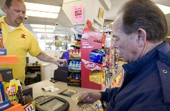 Convenience store clerk Jeff Johnson sells two scratch off lottery tickets to Albert Atwood in Nashville.