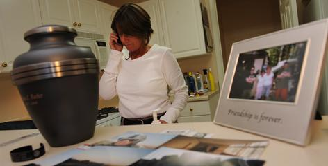 Kelly Barbaer talks by phone with an Army investigator. Her husband's ashes are in the foreground.