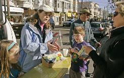 Cynthia Hogan, second from left, sells a Green Zebra entertainment coupon book for a school fundraiser Jan. 10 in San Francisco. Beside Hogan are her daughter Audrey Platt, left, son Philip, and husband Meserve Platt. Hogan pulled her daughter and son out of Catholic school last year.