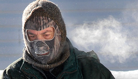 Butch Nelson bundles up against the frigid cold to shovel snow for neighbors in Watertown, Wis., on Tuesday.