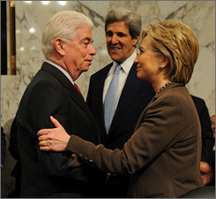 Secretary of State-designate Sen. Hillary Rodham Clinton, D-N.Y., right, is greeted by Senate Foreign Relations Committee member Sen. Christopher Dodd, D-Conn., left, as the committee's chairman Sen. John Kerry, D-Mass.,center, looks on, prior to the start of the committee's hearing on her nomination, Jan. 13, on Capitol Hill in Washington.