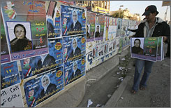 Young Iraqis blanket a wall with campaign posters in Baghdad as nationwide elections approach Jan. 31. About 14,300 candidates are up for 440 legislative seats.