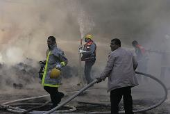 United Nations workers and Palestinian firefighters work to try and put out a fire and save bags of food aid at the United Nations headquarters after it was hit in Israeli bombardment Jan. 15 in Gaza City.