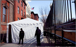 Police officers guard a checkpoint as part of a security perimeter set up around the Blair House, the yellow building with American flag, located steps from the White House.