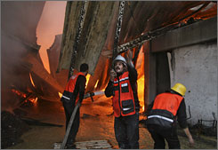 Palestinian firefighters work to extinguish a blaze at a United Nations aid warehouse in Gaza City that came under Israeli shelling Thursday.
