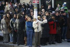 Onlookers brave the cold as they try to catch a glimpse of President-elect Barack Obama after his motorcade arrived at the offices of The Washington Post on Thursday.