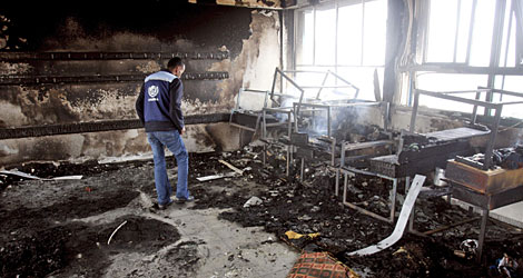 A Palestinian United Nations worker inspects the damage to a classroom at a United Nations school that was hit by shelling on Saturday.