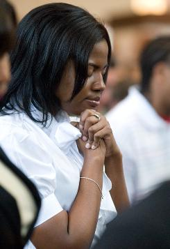 Shaniece Iverson, 26, of Atlanta, prays with the congregation Sunday at Ebenezer Baptist Church, where Martin Luther King Jr. preached before his death in 1968. Raphael Warnock, senior pastor at the church, spoke of King and Barack Obama's election.