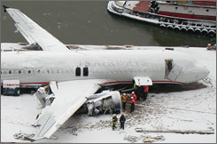 Workers inspect US Airways Flight 1549 after it was lifted from the Hudson River and placed aboard a barge Sunday in New York.