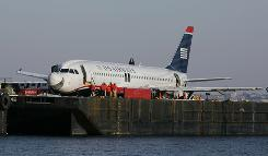 Inspectors examine items removed from US Airways Flight 1549 as it sits on a barge Tuesday at Weeks Marina in Jersey City.