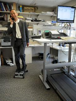 Endocrinologist James Levine gets a little exercise while working at the Mayo Clinic in Rochester, Minn., Jan. 19. Levine says many people are victims of electronic living  to get himself moving, he built his desk around a treadmill and conducts all his meetings while going for a walk.