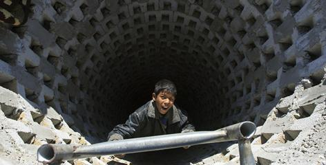 A boy climbs a smuggling tunnel on the Palestinian side of the Gaza-Egypt border. Israel says it destroyed most of the hundreds of smuggling tunnels in repeated airstrikes.