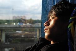 A Karen refugee watches the skyline roll by as his bus enters Bangkok, the last stop before he reaches his new home in America. 