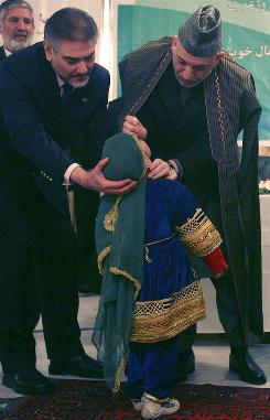 Afghan President Hamid Karzai vaccinates a child from polio in Kabul, Afghanistan, Jan. 11.