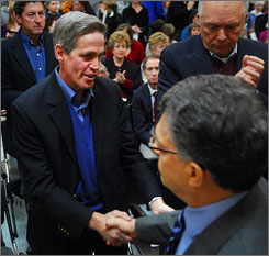 Former Sen. Norm Coleman, R-Minn., shakes hands with Democrat Al Franken on Jan. 11 in St. Louis Park, Minn., after a a gathering at the community center.