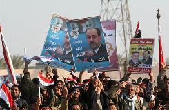 Iraqis wave their national flag and hold placards for the upcoming provincial elections bearing portraits of Prime Minister Nuri al-Maliki in al-Mina near Basra on Friday. Maliki appealed today for strong voter turnout in next week's provincial elections, but the killing of at least eight members of a Sunni family highlighted the country's fragile security situation.