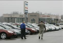 Gary Houser Jr., right, and Rex Dugan talk as they walk the lot at Danville Chrysler Dodge Jeep. The two own dealerships close by each other; they often share sales and costumer mailings.