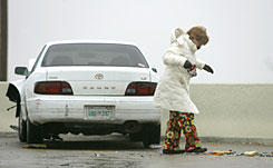 An unidentified women tries to keep her balance after the car she was in was involved in a minor accident near Hefner Road in Oklahoma City on Monday.