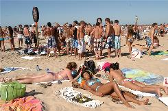 "Spring breakers enjoy the sunshine on the beach at South Padre Island, Texas, in March 2007. Dermatologist Robert Weiss says he often spots melanoma in the thigh zone ""right between where shorts and a bathing suit would hit,"" suggesting that rarely tanned skin is most at risk when exposed to a sudden dose of sun  like on spring break."