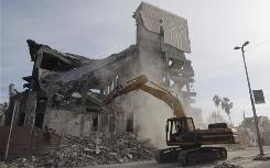 A bulldozer removes rubble from the destroyed Parliament building, which was hit Tuesday during Israel's latest strike on Gaza.
