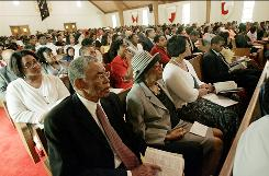 "New Hope Baptist Church Deacon Jesse McGee, front, and his wife, Warine, attend services on a Sunday in May 2008 in Jackson, Miss. In Mississippi, 85% of those surveyed said yes when asked ""Is religion an important part of your daily life?"""