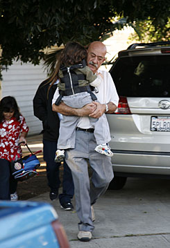 A man escorts two children to a bus Friday morning from the Whittier, Calif., home of a woman who gave birth to octuplets this week. The family says the woman has six other young children at home.