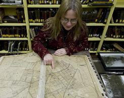 Sue Borders, director of Darby Free Library, shows a 1909 Darby Borough map in the historical room at the library.