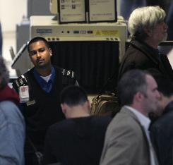 Rupesh Persaud, left, a behavior detection officer with the Transportation Security Administration, watches passengers at a security checkpoint at Newark Liberty International Airport in New Jersey in October.